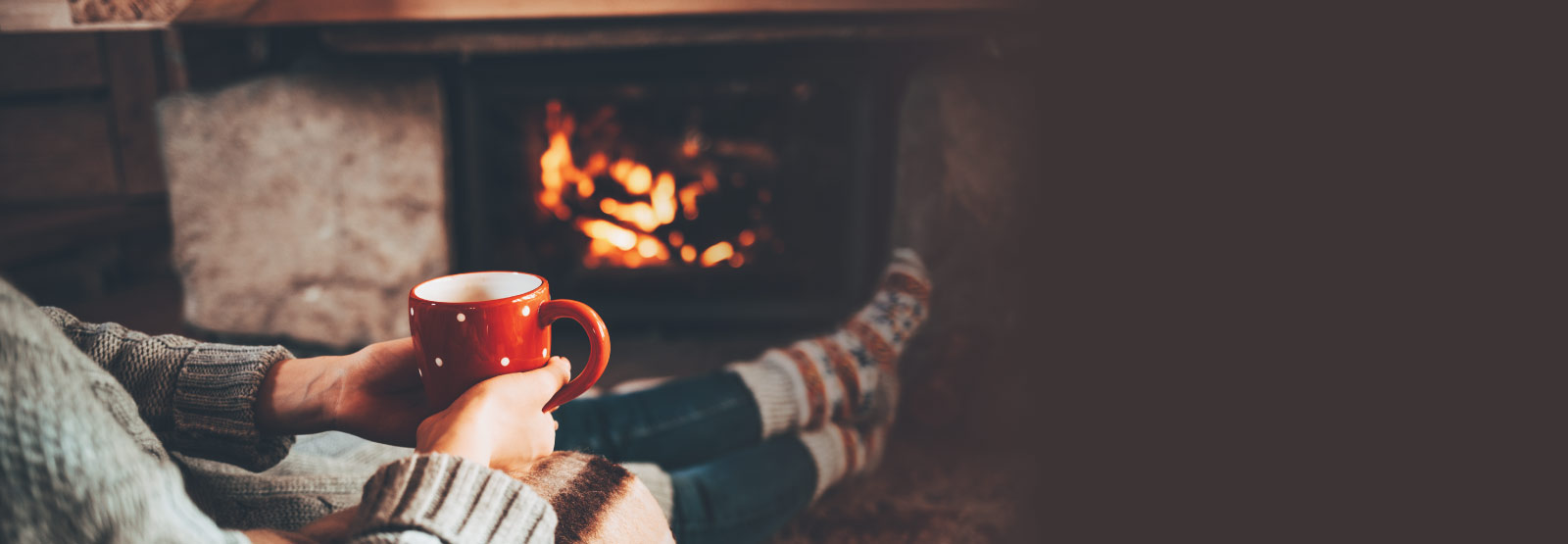 Woman holding red cup of coffee next to fireplace